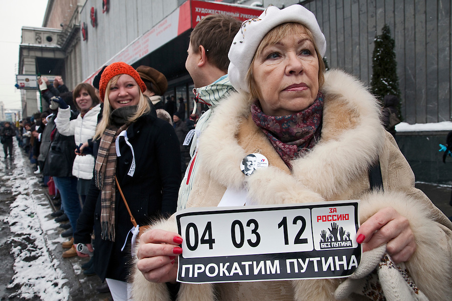 Moscow, Russia, 26/02/2012..An opposition protester holds a car sticker with the date of the Russian presidential election and slogans calling for Putin to resign. Tens of thousands of people formed a 16-kilometre [10-mile] human chain along Moscow's Garden Ring Road in the latest protest against Prime Minister Vladimir Putin and his presidential election campaign. Opposition activists estimated that they needed 34,000 people to complete the chain and symbolically encircle central Moscow.