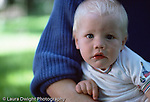 baby boy 10 mos. old closeup, in mother's lap, wary of stranger (stranger anxiety)