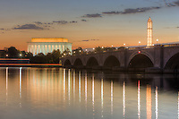 The Arlington Memorial Bridge spans the Potomac River at dawn leading to the Lincoln Memorial, with the illuminated, scaffolding-clad, Washington Monument in the background.