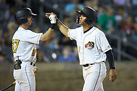 Calvin Mitchell (34) of the West Virginia Power celebrates with teammate Chris Sharpe (27) after scoring a run during the game against the Lexington Legends at Appalachian Power Park on June 7, 2018 in Charleston, West Virginia. The Power defeated the Legends 5-1. (Brian Westerholt/Four Seam Images)