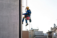Milano, periferia nord, ristrutturazione della facciata di un palazzo. Muratore lavora sospeso da una fune --- Milan, north periphery, renovation of a building's facade. Worker suspended from a rope