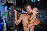 Burmese refugees in Phuket, Thailand. Many of the men spend a day, a week or up to a month out at sea on precarious fishing boats, earning about $200 a month, while the women work at the port or at home scaling and sorting fish. A man kisses his grandson goodbye as he's about to leave on a ship for a few weeks.