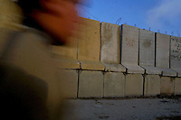 A Palestinian boy walks next to the Abu Dis separating wall, in the outskirts of Jerusalem, February 23, 2003. Photo by Quique kierszenbaum