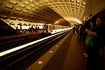 A subway train pulls into the Metro Center station in the US captiol city Washinton DC. People wait for a train on the platform. The shadow of the approaching train moves along the arched ceiling.