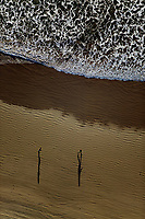 aerial photograph of a couple running on a California beach in the late afternoon