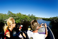 Tourists enjoy an airboat ride in Everglades City, Florida while taking pictures on Holiday vacation