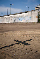 Remains of the Berlin Wall and the shadow of a cross at the Berlin Wall Memorial.