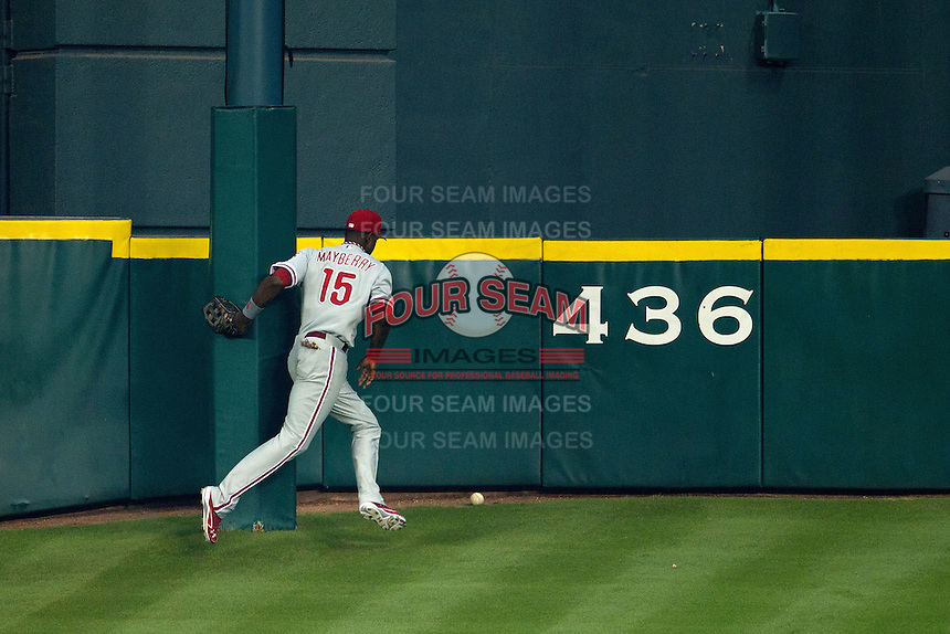 """Philadelphia Phillies outfielder John Mayberry #15 chases a ball hit by JD Martinez around the Minute Maid Park flag pole located on """"Tal's hill"""" during the third inning of Major League baseball game against the Houston Astros on September 16th, 2012 in Houston, Texas. Martinez recorded a triple and the Astros defeated the Phillies 7-6. (Andrew Woolley/Four Seam Images)."""