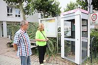 Sylvia Tausend und Karl-Heinz Wamser an der ramponierten Telefonzelle in Wallerstädten