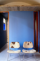 In one of the bedrooms a pair of cow-hide chairs is arranged against a bright blue wall