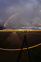 Tailwheel ferry pilot Herb Lingl casts a long shadow at sunset while photographing at the Petaluma Municipal Airport, (O69) in Petaluma, Sonoma County, California.  The moisture from a passing winter storm creates a dramatic rainbow.
