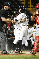 Bradenton Marauders third baseman Walker Gourley (5) hugged by outfielder Jeff Roy (2) after sliding in safely with the game winning run during a game against the Palm Beach Cardinals on April 8, 2014 at McKechnie Field in Bradenton, Florida.  Bradenton defeated Palm Beach 4-3.  (Mike Janes/Four Seam Images)
