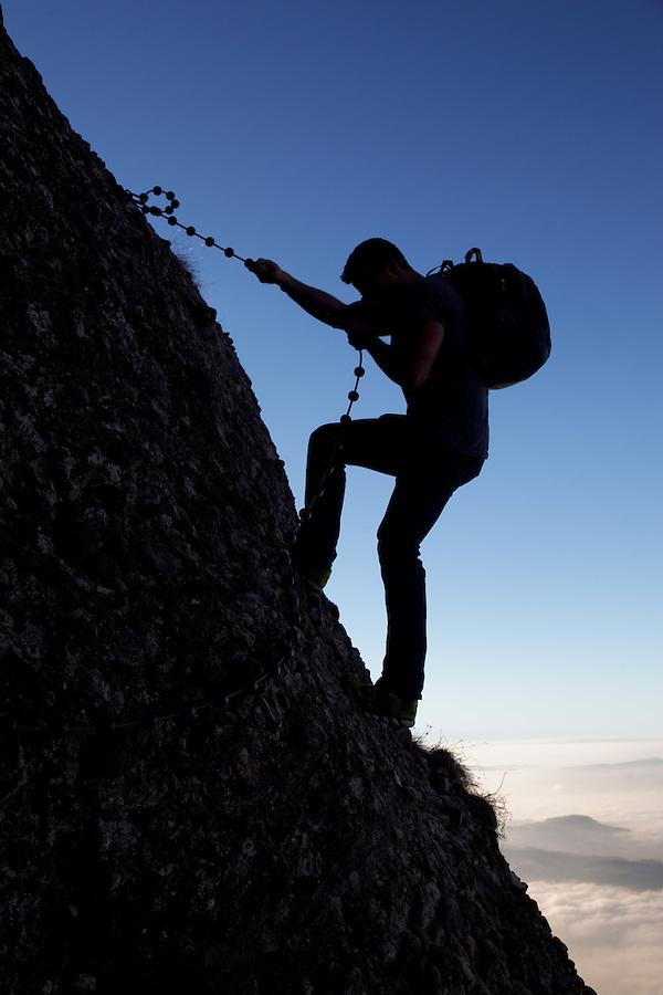 Man rappelling on the Arschbagge near summit of Mount Rigi, Bänderenweg route, Switzerland, Europe