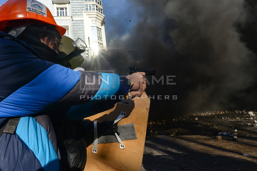 A hooded protester pointing a gun during the intense clashes in Maidan Square. Kiev, Ukraine