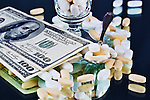 Drugs and Money.  Legal prescription drugs represented with U.S. currency, silver spoon and  desert glass. Conceptual image representing drug culture, medical, insurance, dichotomy, and more.