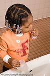 Educaton preschool  3-4 year olds girl standing at sink brushing teeth hair in braids vertical