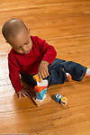 18 month old toddler boy sitting playing with blocks and spindle toy
