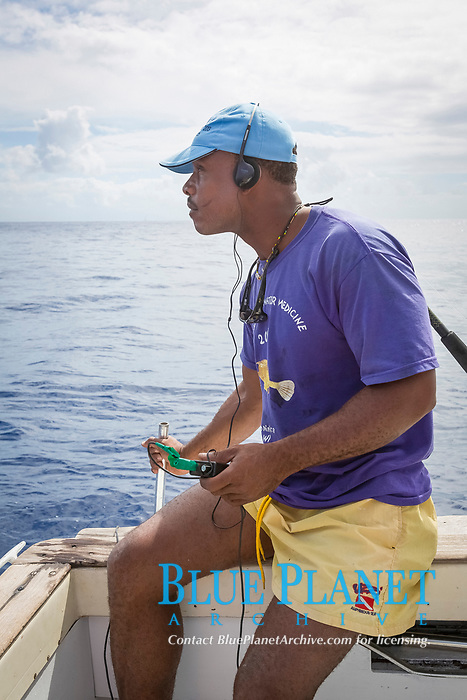 Jerry the skipper, listening to his hydrophone to keep track of sperm whales, Dominica, Caribbean Sea, Atlantic Ocean
