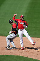 Philadelphia Phillies infielder Chris Nelson (27) throws to first over Joe Walsh (35) during an exhibition game against the University of Tampa on March 1, 2015 at Bright House Field in Clearwater, Florida.  University of Tampa defeated Philadelphia 6-2.  (Mike Janes/Four Seam Images)