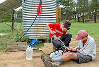 Photo story of Philmont Scout Ranch in Cimarron, New Mexico, taken during a Boy Scout Troop backpack trip in the summer of 2013. Photo is part of a comprehensive picture package which shows in-depth photography of a BSA Ventures crew on a trek. This photo show BSA Venture Crew members working together to use a water filtration pump to filter untreated water at their  remote campsite in the backcountry of the Philmont Scout Ranch.<br /> <br /> The  Photo by travel photograph: PatrickschneiderPhoto.com