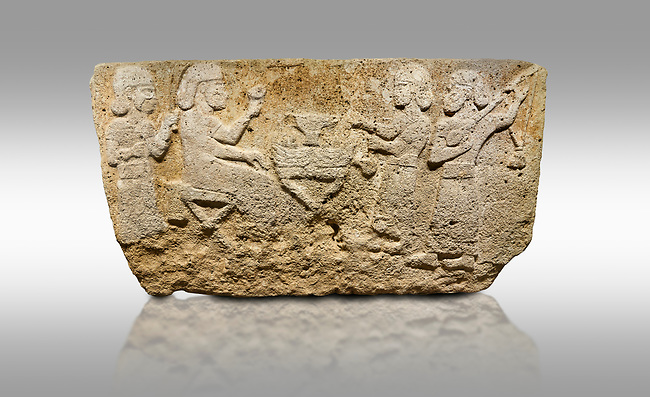Picture & image of Hittite monumental relief sculpted orthostat stone panel from Water Gate Limestone, Karkamıs, (Kargamıs), Carchemish (Karkemish), 900-700 BC.  Anatolian Civilisations Museum, Ankara, Turkey.<br /> <br /> The figure sitting on a stool to the left of the table holds a goblet in his right hand which he raised upwards. Behind, there is a servant with a fan in his hand. On the other side of the table is another servant waits with a vessel in the hands. The rightmost figure plays a Saz (a stringed musical instrument) with the tassel on the handle. <br /> <br /> On a gray background.