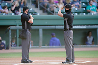 Umpires Adam Clark, left, and Clay Williams await the start of a game between  of the Greenville Drive and Brooklyn Cyclones on Saturday, May 15, 2021, at Fluor Field at the West End in Greenville, South Carolina. (Tom Priddy/Four Seam Images)