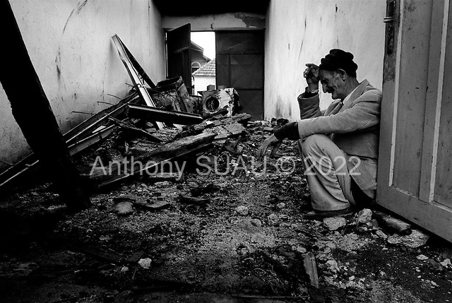 Podujevo, Kosovo  <br /> 1999<br /> <br /> A man sits crying endlessly in his shop and house after returning to find it completely burnt down and three of his five sons decapitated and burnt by Serbian gunmen.