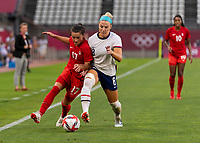 KASHIMA, JAPAN - AUGUST 2: Jessie Flemming #17 of Canada and Julie Ertz #8 of the USWNT battle for the ball during a game between Canada and USWNT at Kashima Soccer Stadium on August 2, 2021 in Kashima, Japan.