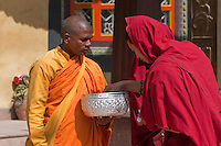 """Bodhnath, Nepal.  A Buddhist Monk Receives an Offering in front of the Tamang Gompa (Monastery).  Note """"I (Love) Tibet"""" Sticker on the Bowl."""