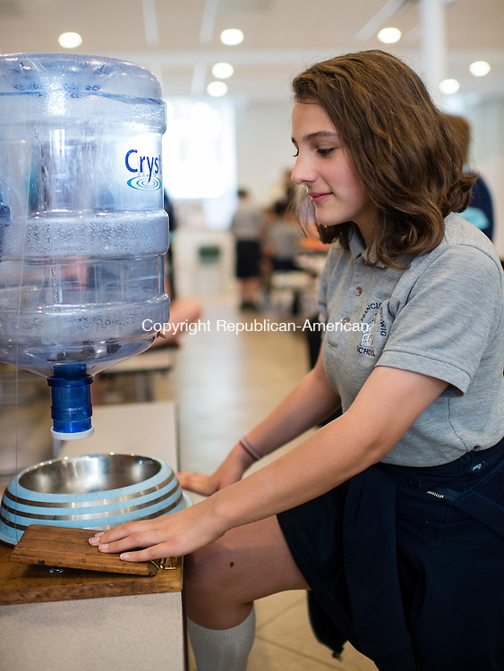 """NAUGATUCK, CT- 20 May 2016-052016EC02-  Angelina Gregory, a student at St. Francis – St. Hedwig School in Naugatuck, demonstrates her invention, the """"Jug A Dog."""" The fifth grader thought of the idea for families who go away for days at a time and leave their pet home. The dog puts its paw on a wooden lever to the left and refills water from the upside down jug. There were 38 total inventions from fourth and fifth graders Friday. The students started working on the projects in February. Their goal was to solve problems they saw in their community. Erin Covey Republican-American"""