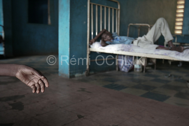 """© Remi OCHLIK/Ip3press.com; Freetown, Sierra Leone  le 29 novembre 2004 - Le Kissy Mental Hospital est le seul etablissement psychiatrique de la Sierra leone. Il recueille les personnes souffrant de skyzophrenie, les alcooliques ou les anciens drogues. Il est aussi un refuge pour ceux qui ont souffert de la guerre. ......Kissy mental hospital directed by doctor  E. A. Nahim, is the only mental hospital in Sierra Leone. Patients are mostly suffering from schizophrenia, alcohol and drugs deceases or from war aftermath. People are chained to their """"beds"""", most of them are hold in the hospital for several years. There is no medecine and no food enought..."""