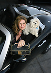Ivette Dominguez, president of Alpine GMC in Littleton, sits in a 2008 convertible Pontiac Solstice GXP Turbo in front of the car dealership, with her dog, Simba, and her purse.  Fashion story about women and their purses.  (ELLEN JASKOL/ROCKY MOUNTAIN NEWS)