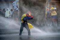 BOGOTA - COLOMBIA, 20-07-2021: Un miembro de primera línea trata de resistir el chorro de agua de una tanqueta durante los disturbios entre manifestantes y miembros del ESMAD de la policía en el sector de Usme hoy, 20 de julio de 2021, en Bogotá durante la conmemoración del día de independencia de Colombia en el cual siguen las protestas del paro nacional que nuevamente convocó movilizaciones para protestar por el gobierno del presidente Duque. / A member of the front line tries to resist the jet of water from a tank during the riots between protesters and members of the ESMAD of the police in the Usme sector today, July 20, 2021, in Bogotá during the commemoration of Colombia's independence day in which the protests of the national strike that again called mobilizations to protest the government of President Duque. Photo: VizzorImage / Diego Cuevas / Cont