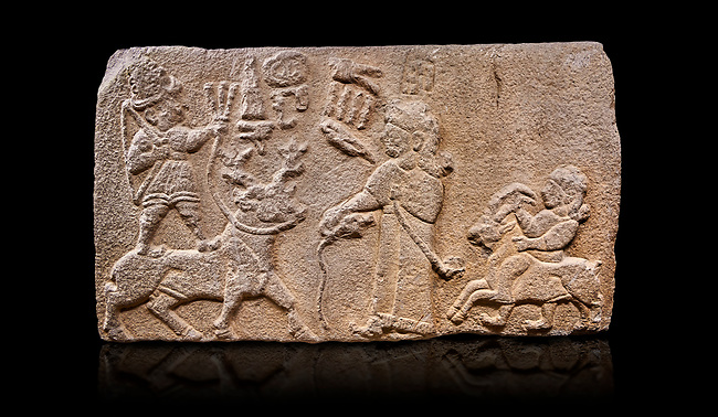 "Aslantepe Hittite relief sculpted orthostat stone panel. Limestone, Aslantepe, Malatya, 1200-700 B.C. Anatolian Civilisations Museum, Ankara, Turkey.<br /> <br /> Scene of king's offering drink and sacrifice to the god. The god is on the deer, with the bow attached to his shoulder and with a triple bundle of lightning in his hand. The king looks at the god, and makes the libation to the god while carrying a scepter with a curled end - lituus. Behind the king is a servant holding a goat for sacrifice to the god. Hieroglyphs read; ""God Parata, Strong King... "". <br /> <br /> Against a black background."