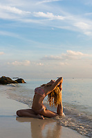 Beach yoga in Ko Lipe island Thailand, girl in pigeon pose