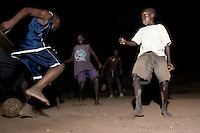 A group of older boys play soccer with a staff member at the Doctors Without Borders (MSF; Medecins Sans Frontieres) tent compound. This compound is one of the few places children, known as Night Commuters, can find protection every  night to avoid being abducted by the Lords Resistance Army (LRA) in Northern Uganda. The LRA is primarily made up of abducted youth. Night Commuters find much more than safety in the compounds, they also find friendships, activity and fellowship. Tens of thousands of children, on average, make this exodus every evening. The war in Northern Uganda has been transpiring for two decades. Lachor, Gulu District, Uganda, Africa. December 2005 © Stephen Blake Farrington