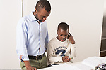 Nine year old boy at home working on homework, writing assignment, assisted by father