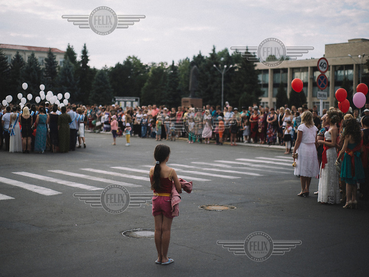 A young girl stands apart from a crowd celebrating the end of the school year.