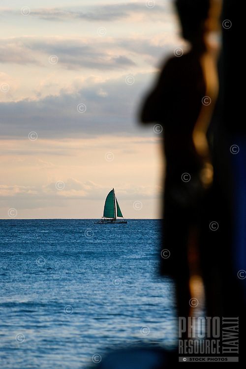 A sailboat passes by Waikiki as the forms of onlookers are illuminated by the setting sun