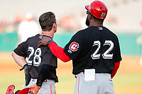 Chattanooga Lookouts catcher Mark Kolozsvary (28) discusses strategy with assistant coach Lenny Harris (22) against the Tennessee Smokies at Smokies Stadium on June 18, 2021, in Kodak, Tennessee. (Danny Parker/Four Seam Images)