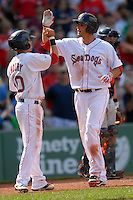 Outfielder Alex Hassan (#28) of the Portland Sea Dogs is greeted at the plate by infielder Ryan Khoury (#10) following his two-run homerun versus the Binghamton Mets during the  2011 Futures at Fenway minor league doubleheader on August 20, 2011 at Fenway Park in Boston, Massachusetts. (Ken Babbitt/Four Seam Images)