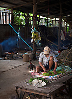 A man preparing food in this old Building, province of Battambang, Cambodia