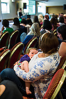 A mother breastfeeding her child while listening to a speaker  at a conference.<br /> <br /> West Midlands, England, UK<br /> 07/06/2014<br /> <br /> © Paul Carter / wdiip.co.uk