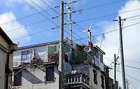 MADAGASCAR Antananarivo, small wind turbine to be independent from Jirama ( Jiro sy rano malagasy) the state-owned electric utility and water services company which often has power failures  / MADAGASKAR Antananarivo, kleine Windkraftanlage zur Eigenversorgung auf einem Wohnhaus um unabhaengig von Stromausfaellen von Jirama, dem staatlichen Stromnetzbetreiber, zu sein