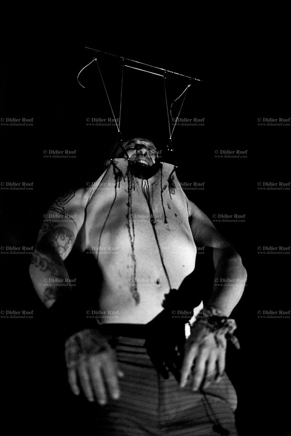 """Switzerland. Canton Valais. Bas-Valais. A man with pain and blood during a chest suspension. A suspension is the act of suspending a human body from hooks that have been put through body piercings. A chest suspension, sometimes incorrectly referred to as an """"O-Kee-Pa"""", is a suspension in which the hook(s) are placed in the chest. Typically two hooks are used for this type of suspension. The suspendee's body is studied to decide the proper placement, number, and size of metal hooks which are pierced into the skin to lift the person off the ground. Depending on the position in which the body is to be suspended, multiple hooks are used. Finding the proper hook placement and number involves basic geometry and an acute understanding of human anatomy and physiology, as well as the durability of the individual's skin. If the number of hooks are too few, the suspended individual's skin will be unable to withstand the body's weight and will rip. The amount of weight that each hook supports must be distributed evenly throughout the entire body. A set of ropes are attached to the hooks in order to slowly and carefully lift an individual off the ground. 23.07.2016  © 2016 Didier Ruef"""