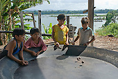Pará State, Brazil. Aldeia Apyterewa (Parakana). Boys playing with spinning tops in the farinha pan.