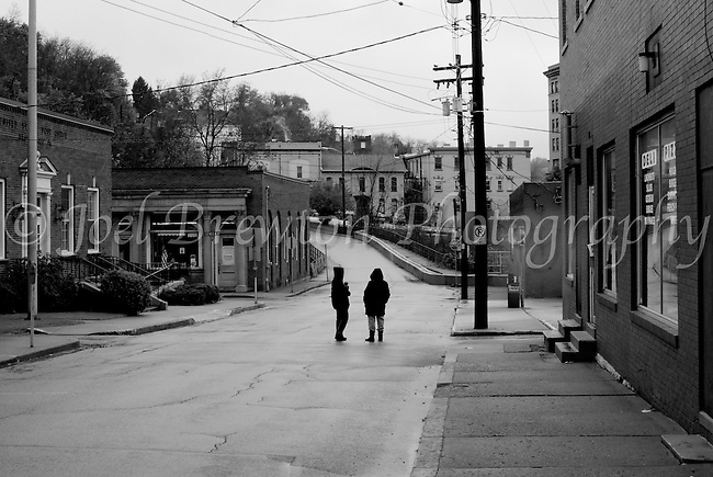 Two lone figures stand in the streets on Brownsville, PA on a cloudy, wet afternoon.