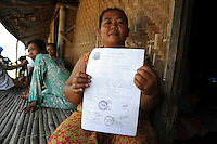 A Besuki villager, now living in a makeshift shack, holds onto a certificate of payment for land and house issued by the local Kepala Desa (Village Head) but which will probably not be legally sufficient to substantiate her claims for total compensation for loss of her home in the mud flow. Since May 2006, more than 10,000 people in the Porong subdistrict of Sidoarjo have been displaced by hot mud flowing from a natural gas well that was being drilled by the oil company Lapindo Brantas. The torrent of mud - up to 125,000 cubic metres per day - continued to flow three years later.