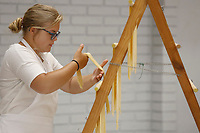 Torrie Pianalto, 15, hangs pasta noodles on a rack to dry Thursday, July 15, 2021, at the St. Joseph's Parish Hall in Tontitown. More than 3,000 pounds of pasta noodles are being prepared for the 122nd Tontitown Grape Festival which runs Tuesday, August 3 through Saturday, August 7. The homemade spaghetti will be served August 5 through 7. Check out nwaonline.com/210716Daily/ and nwadg.com/photos for a photo gallery.(NWA Democrat-Gazette/David Gottschalk)