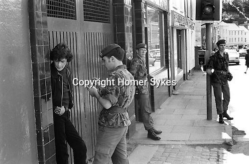 Derry Northern Ireland Londonderry. 1979. British Army taking details of Catholic man in street.
